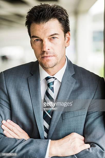 Portrait of serious looking businessman wearing grey suit