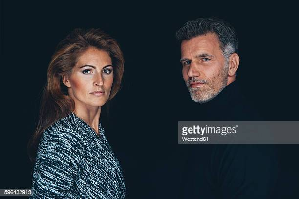 Portrait of serious looking couple in front of black background