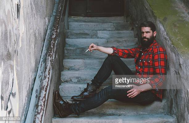 Portrait of serious looking man with cigarette sitting on stairs