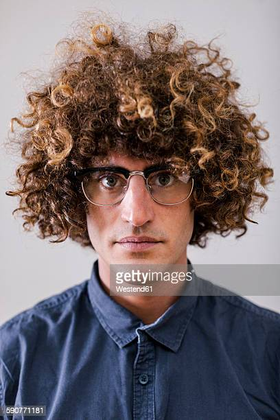 Portrait of serious looking man with curly hair wearing glasses