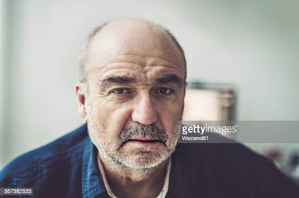 portrait of serious looking senior man - verlegen stockfoto's en -beelden