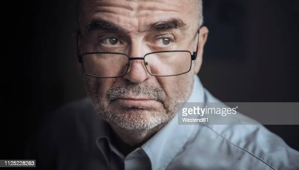 portrait of serious looking senior man wearing glasses - suspicion stock pictures, royalty-free photos & images