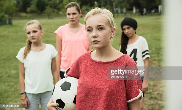Portrait of serious looking teenage girl with soccer ball in front of three other girls