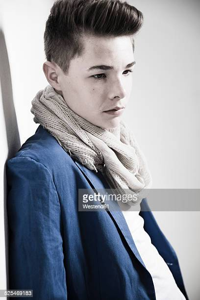 portrait of serious looking teenager leaning against wall - ポンパドール ストックフォトと画像