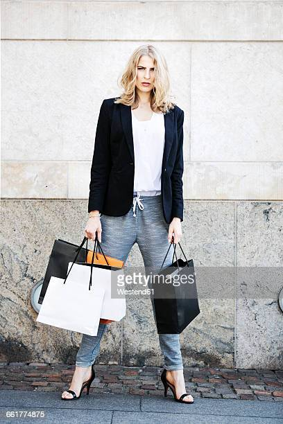 Portrait of serious looking woman with many shopping bags