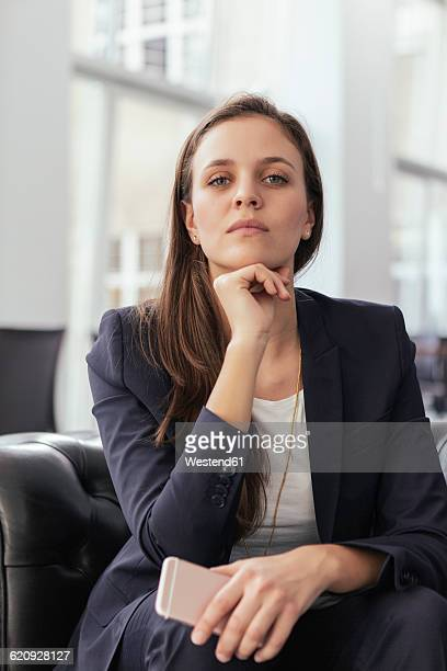Portrait of serious looking young business woman with hand on chin