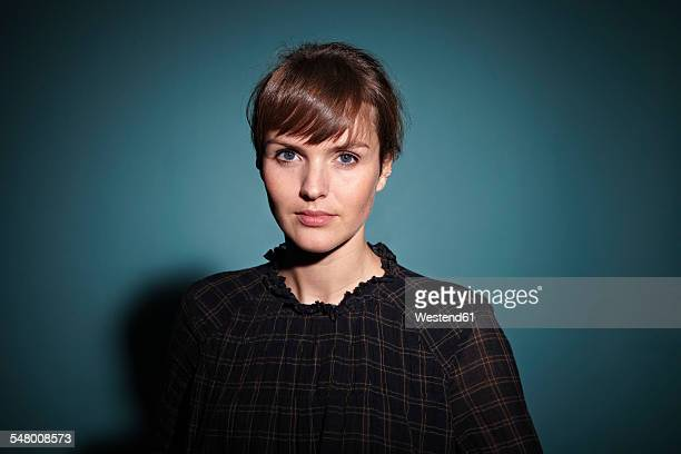 portrait of serious looking young woman in front of blue background - vignettierung stock-fotos und bilder