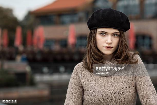 Portrait of serious looking young woman wearing beret and knitted dress