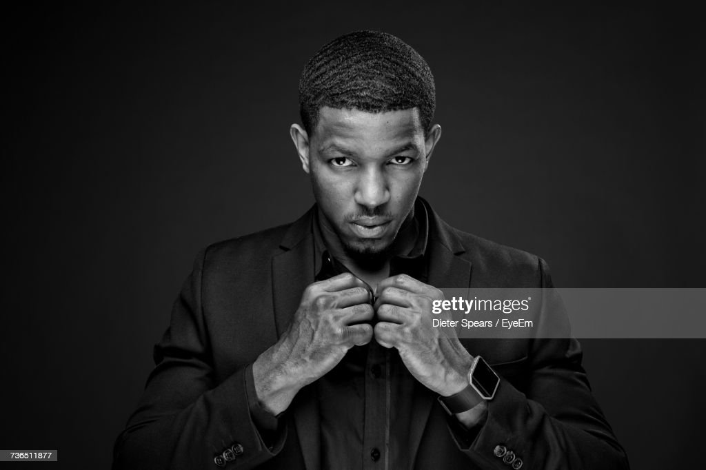 Portrait Of Serious Male Model Buttoning Shirt While Standing Against Black Background : Stock Photo