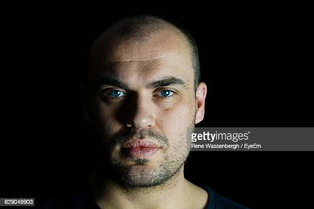 portrait of serious man against black background - blue eyes stock pictures, royalty-free photos & images