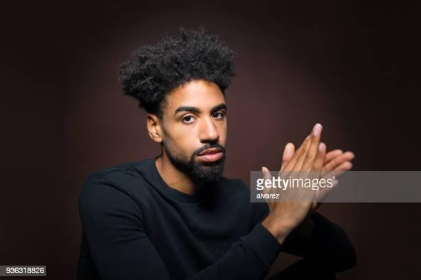 Porträt von ernster Mann mit den Händen umklammert