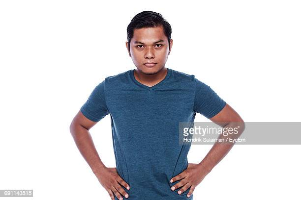 Portrait Of Serious Man With Hands On Hip Standing Against White Background