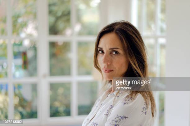 portrait of serious mature brunette woman at the window - 45 49 ans photos et images de collection