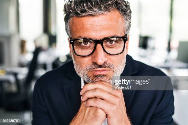 Portrait of serious mature businessman wearing glasses in office