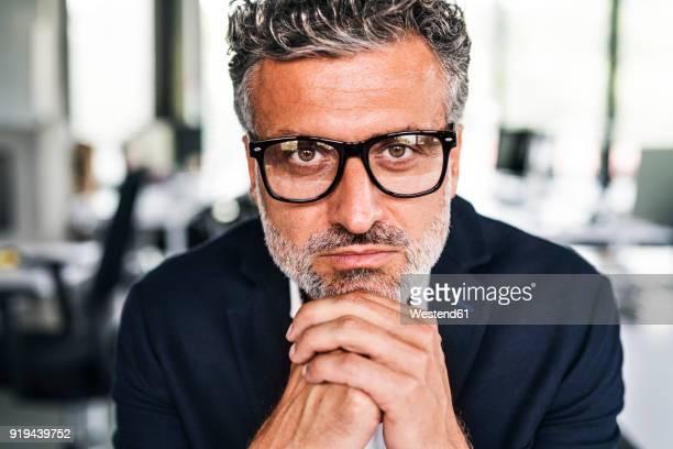 portrait of serious mature businessman wearing glasses in office - gestikulieren stock-fotos und bilder
