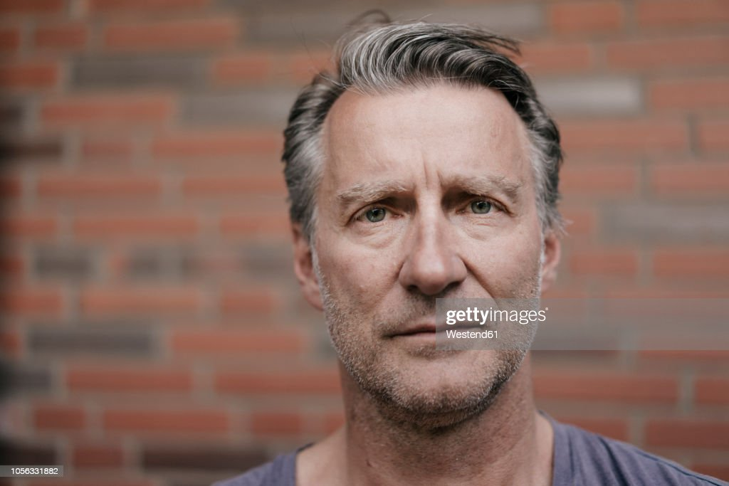 Portrait of serious mature man in font of brick wall : Stock-Foto