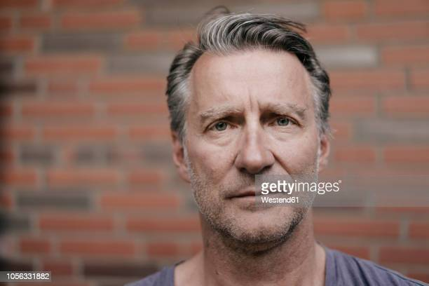 portrait of serious mature man in font of brick wall - mann stock-fotos und bilder