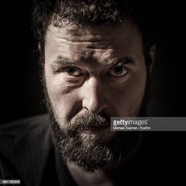 Portrait Of Serious Mid Adult Man With Beard Against Black Background