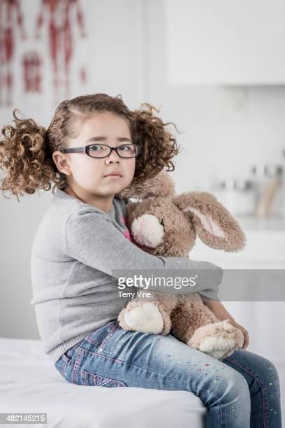 Portrait of serious mixed race girl hugging stuffed animal
