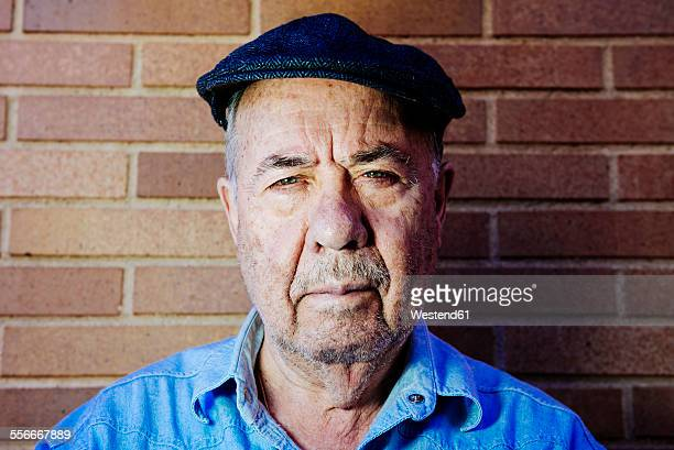 portrait of serious old man wearing beret - flat cap stock pictures, royalty-free photos & images