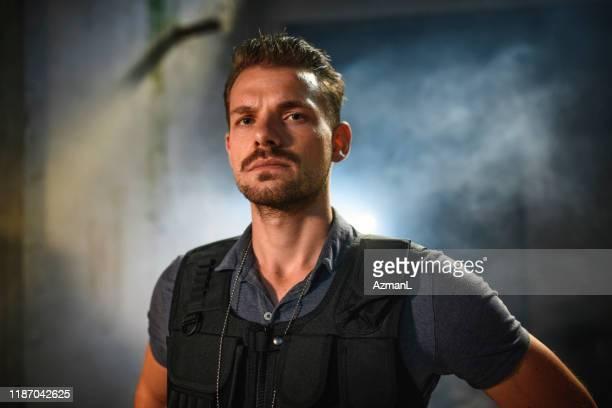 霧の犯罪現場で深刻な警察官の肖像 - 刑事司法 ストックフォトと画像