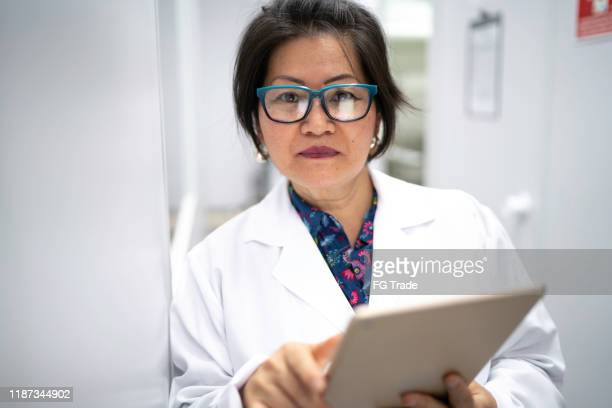 portrait of serious scientist holding digital tablet - microbiologist stock pictures, royalty-free photos & images