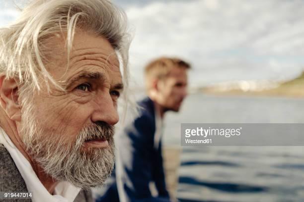 portrait of serious senior man at a lake with man in background - suspeita - fotografias e filmes do acervo