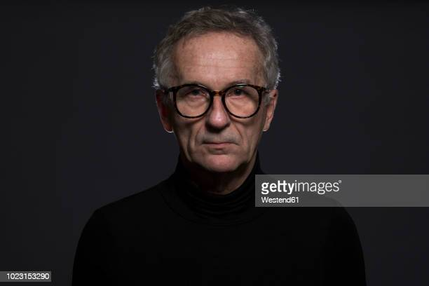 portrait of serious senior man wearing glasses in front of dark background - dark clothes stock photos and pictures