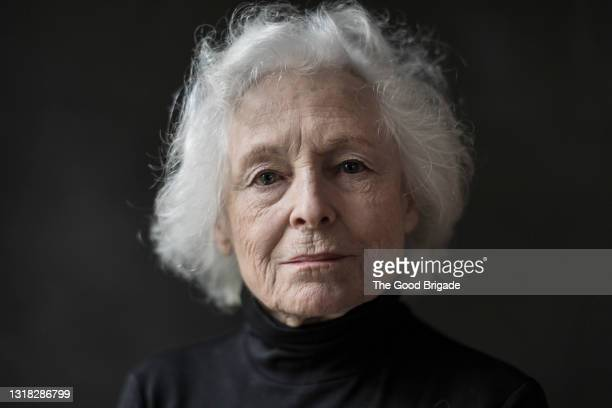portrait of serious senior woman against black background - senior adult stock pictures, royalty-free photos & images