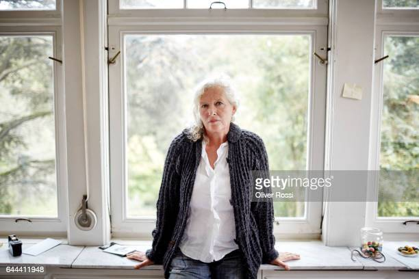 portrait of serious senior woman at the window - alleen één seniore vrouw stockfoto's en -beelden