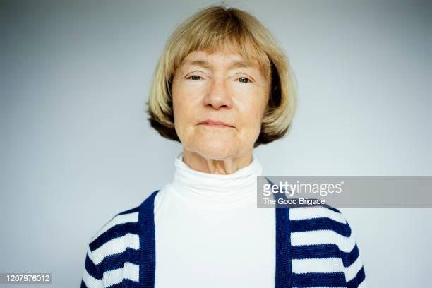 portrait of serious senior woman on white background - heck stock-fotos und bilder
