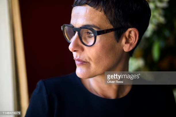 portrait of serious short-haired woman wearing glasses looking away - introspection stock pictures, royalty-free photos & images