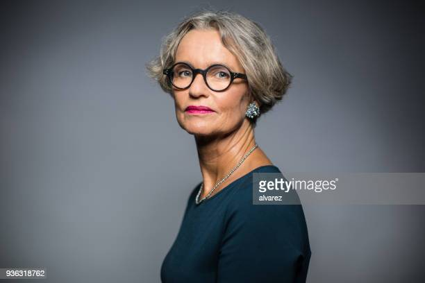 retrato de mujer seria contra el fondo gris - retrato formal fotografías e imágenes de stock