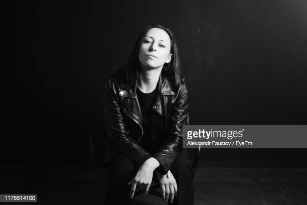 portrait of serious woman sitting against black background - three quarter length stock pictures, royalty-free photos & images