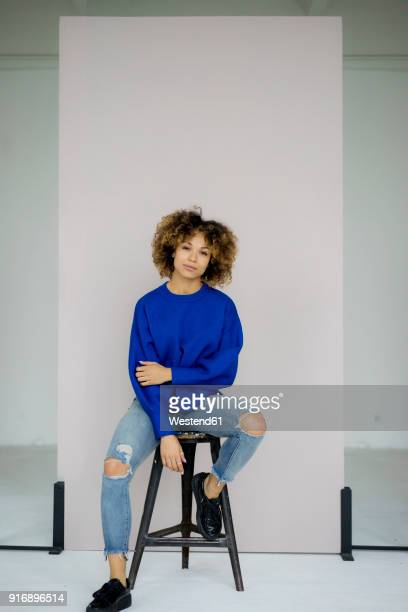 portrait of serious woman wearing blue pullover sitting on stool - sitzen stock-fotos und bilder