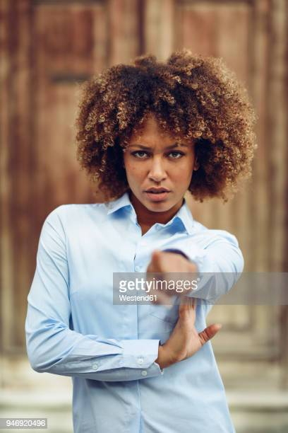 Portrait of serious woman with afro hairstyle pointing with her finger outdoors