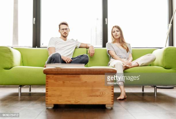 portrait of serious young couple sitting on couch in living room at home - sofá fotografías e imágenes de stock