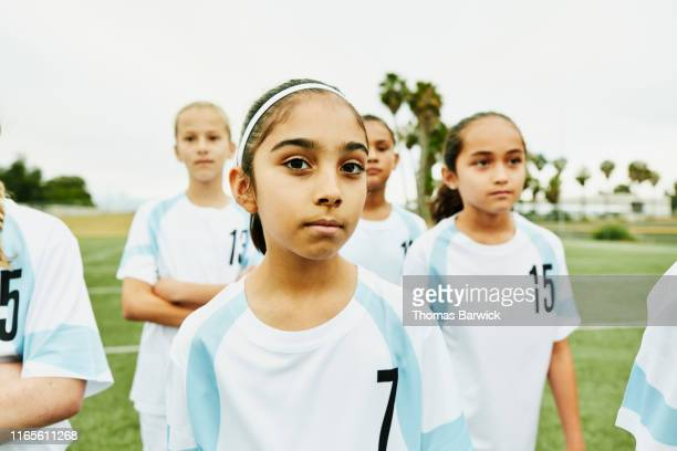 portrait of serious young female soccer player standing on field with teammates - traje de fútbol fotografías e imágenes de stock
