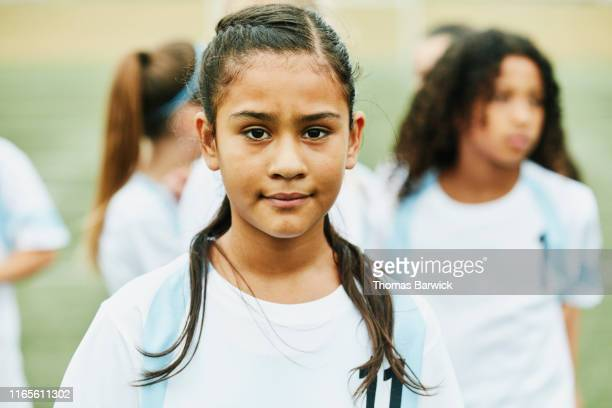 portrait of serious young female soccer player standing on field with teammates before game - pre adolescent child stock pictures, royalty-free photos & images