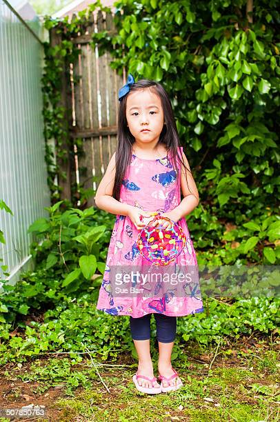 portrait of serious young girl in garden with toy - korean ethnicity stock pictures, royalty-free photos & images