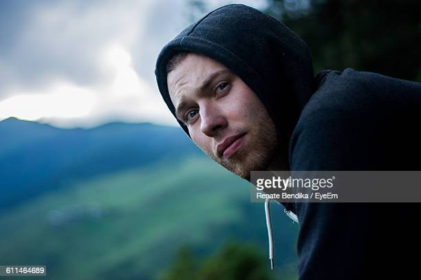Portrait Of Serious Young Man Wearing Hood Against Mountains