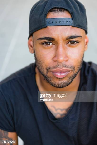 Portrait of serious young man with stubble wearing basecap