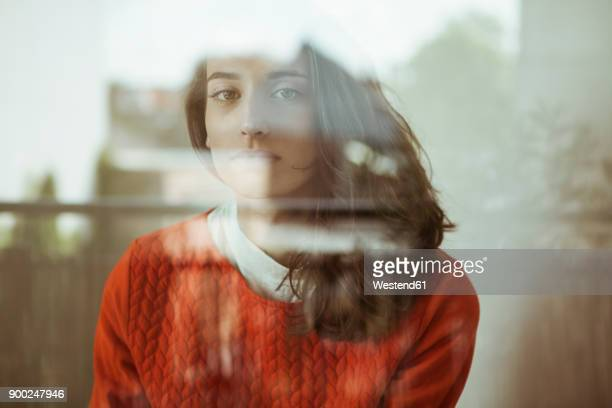 portrait of serious young woman behind glass pane - spiegelung stock-fotos und bilder