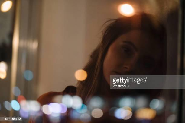 portrait of serious young woman behind windowpane - traurigkeit stock-fotos und bilder