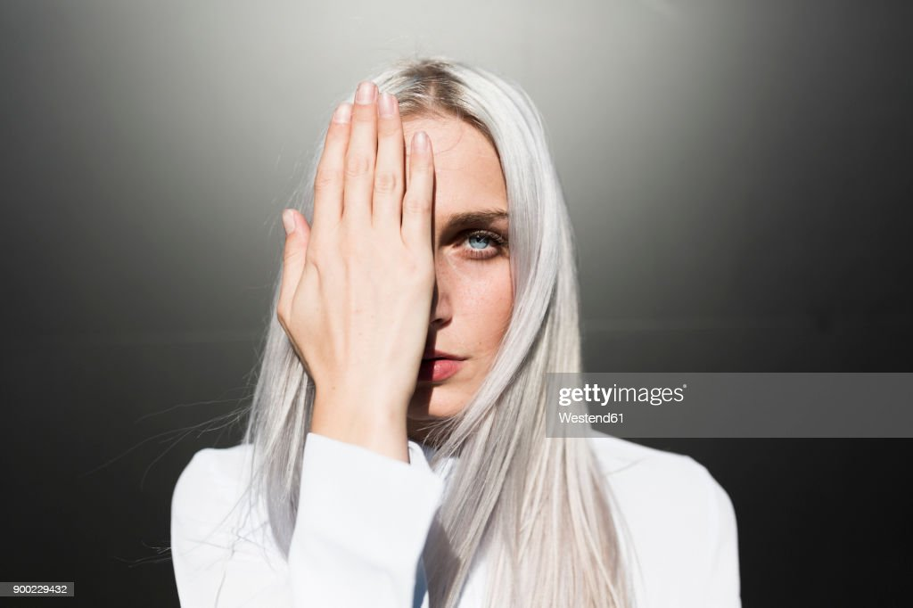 Portrait of serious young woman covering one eye : Stock Photo