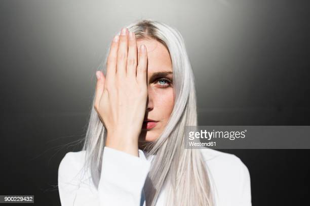 Portrait of serious young woman covering one eye