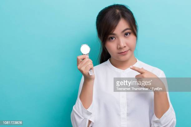 Portrait Of Serious Young Woman Pointing At Wristwatch Against Blue Background
