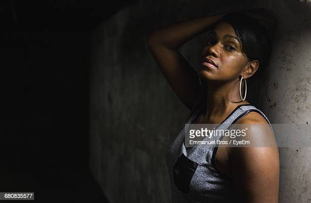 Portrait Of Serious Young Woman Posing By Old Wall In Darkroom