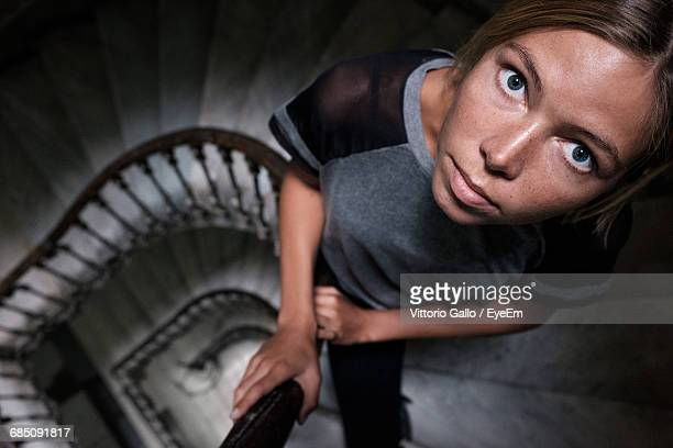 Portrait Of Serious Young Woman Standing On Steps In Building