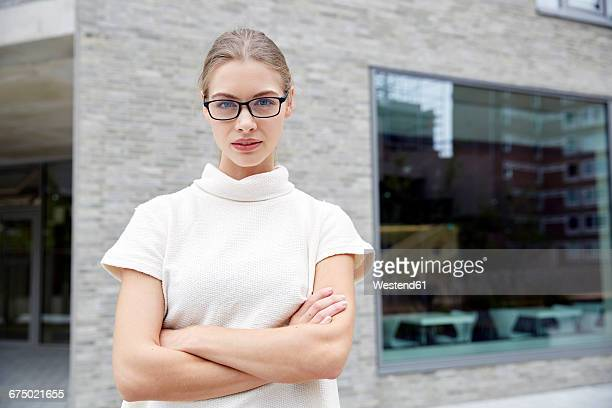 Portrait of serious young woman with arms crossed